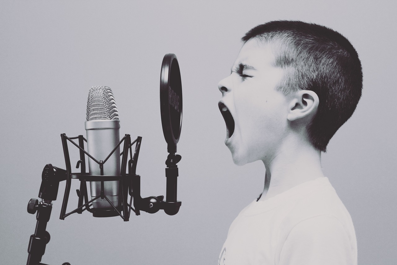 Boy screaming into old fashioned microphone